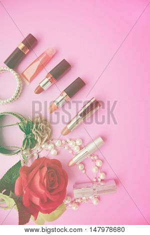 Decorative flat lay composition with colorful lipstick pearl and flowers. Top view on pink background.