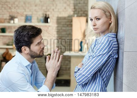Young man asking sulky girlfriend's forgivenes at home on bended knees.