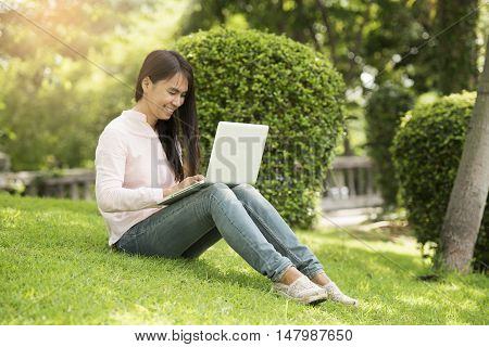Young beautiful woman working outdoor in a public park. Working on laptop outdoors. Cropped image of female working on laptop while sitting in a park.