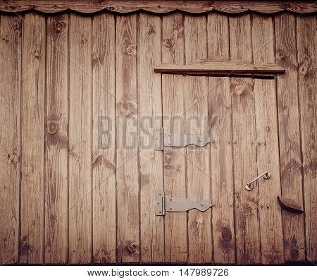 Small old wooden door of village well dark vertical boards. Vintage effect.