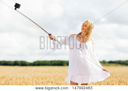 technology, summer holidays, vacation and people concept - smiling young woman in white dress taking picture by smartphone selfie stick on cereal field