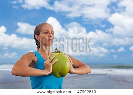 Woman fitness exercise with raw coconut as weight to keep fit and health. Ocean beach surf background. Healthy lifestyle sport activity and natural flesh on summer family holiday in tropical island.