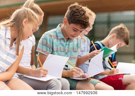 primary education, friendship, childhood, communication and people concept - group of happy elementary school students with notebooks sitting on bench outdoors
