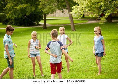 friendship, childhood, leisure and people concept - group of happy kids or friends playing game in summer park