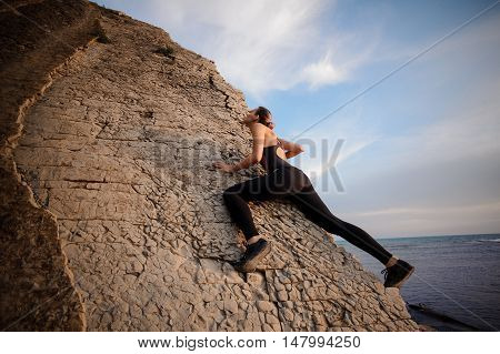 Athletic young pretty girl rock climbing without carbines and rope, bouldering. looking up