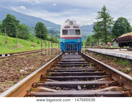 Old train on the railroad tracks on the provincial railway station in the Carpathian mountains at summer evening