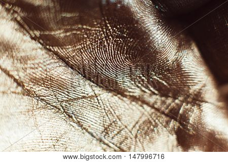 Patterns on golden human palms close-up. Painted hand with gold leaf. Gilded arm. Luxury body art