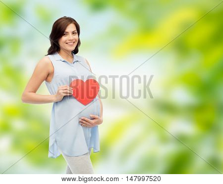 pregnancy, love, people and expectation concept - happy pregnant woman with red heart shape touching her belly over green natural background