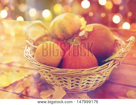 harvest, season, halloween and autumn concept - close up of pumpkins in wicker basket with leaves on wooden table over holidays lights