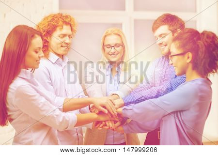 business, office, gesture and startup concept - smiling creative team with hands on top of each other sitting in office