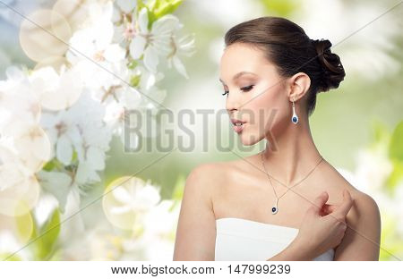 beauty, jewelry, wedding accessories, people and luxury concept - beautiful asian woman or bride with earring and pendant over natural spring cherry blossom background