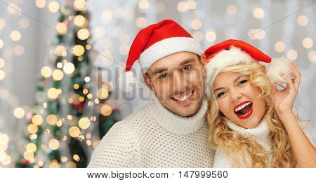 people, christmas, holidays and new year concept - happy family couple in sweaters and santa hats over lights background