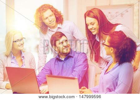 business, office and startup concept - smiling creative team with with laptop computers working in office