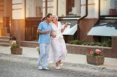 Mature couple walking and smiling. Man and woman holding hands. Cheerful stroll at daytime. Cherish every moment together. poster