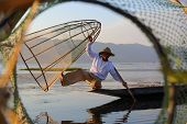 Myanmar travel attraction landmark - Traditional Burmese fisherman with fishing net at Inle lake in Myanmar famous for their distinctive one legged rowing style poster