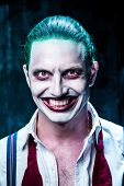 Bloody Halloween theme: The crazy joker face on black background poster