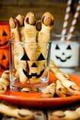 Halloween witch's fingers cookies. Homemade cookies in the form of terrible human fingers decoration almond nail for treat kids for Halloween party selective focus poster