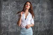 young sexy desire woman teacher near blackboard with maths formula poster