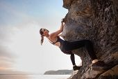 Young female rock climber climbing challenging route on overhanging cliff . Summer time. poster