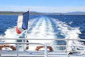 French tricolour flag flying on the back of a boat leaving a wake through the blue Mediterranean sea in summer poster