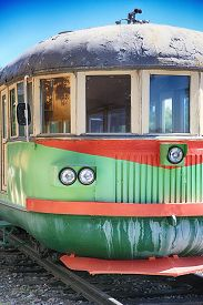 Rusty, shabby, old electric train. With round headlights and wooden windows.