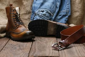 Men's shoes jeans leather belt on a background of wooden planks with space for text