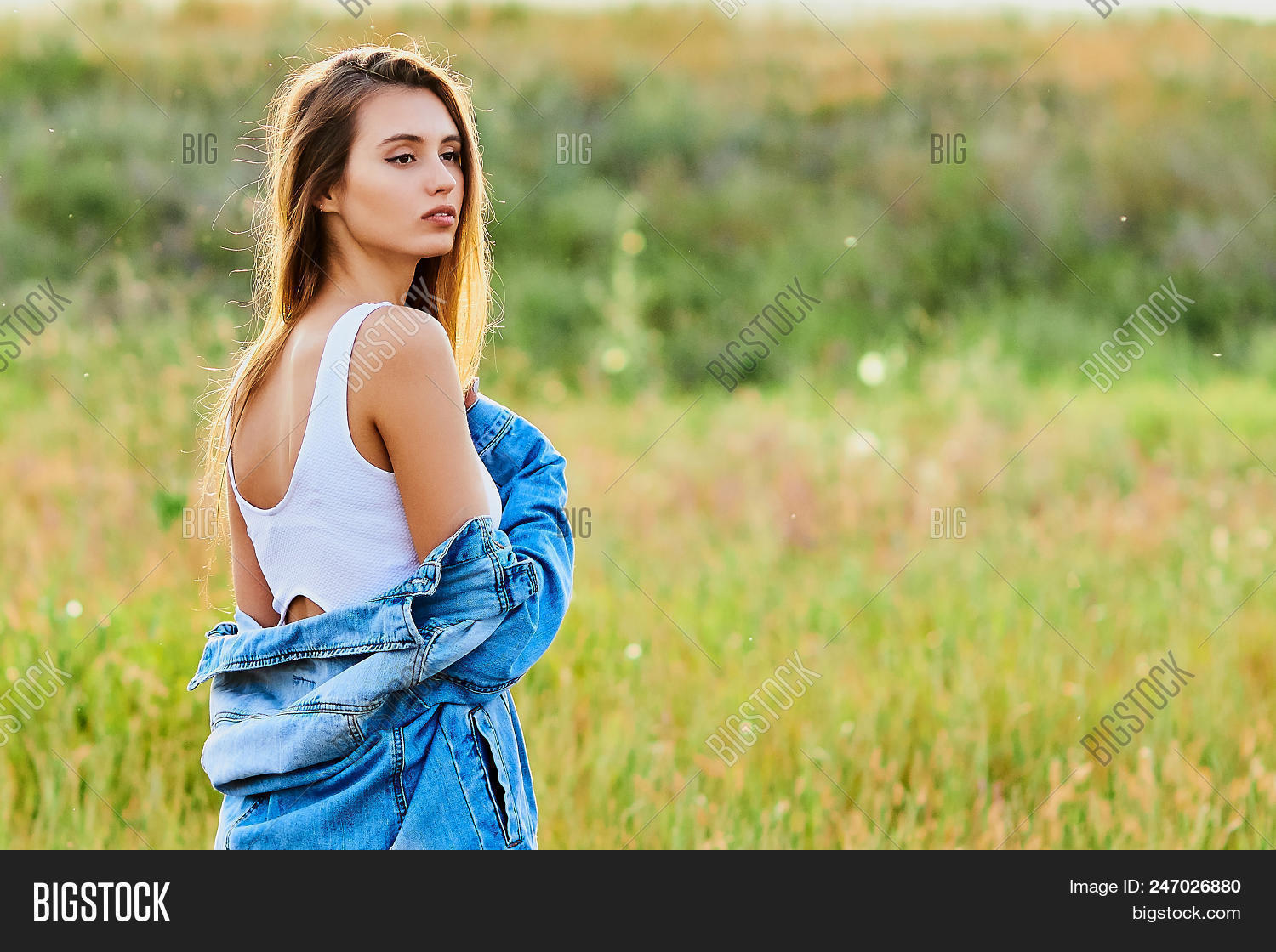 5a5c8e7e52 Happy Smiling Young Girl Wearing Blue Jeans Jacket And White Dress Is  Standing In The Field