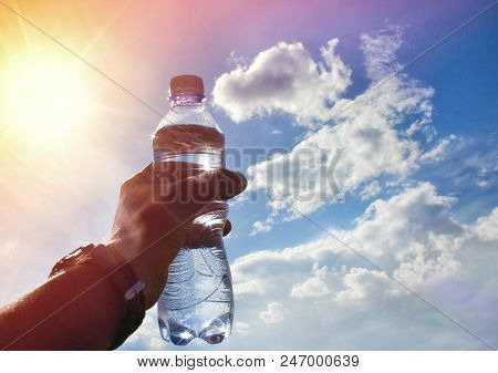A Bottle Of Water In A Hand Against The Sky And Sun. Drinking Water. Drinking Water At Dawn. Drinkin
