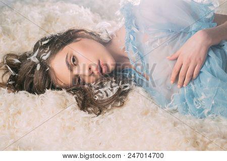 Tender Pretty Girl Enjoying Soft Embrace Of Fluffy Bed. Beautiful Female In Blue Lace Nightgown Lyin
