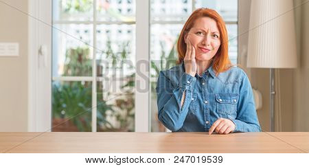 Redhead woman at home touching mouth with hand with painful expression because of toothache or dental illness on teeth. Dentist concept.