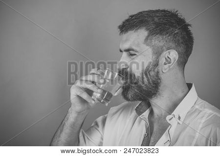 Health and dieting. Life source and healthcare. Hangover and thirst. Man with long beard hold water glass on green background. Hipster drink clean healthy water, refreshing. poster