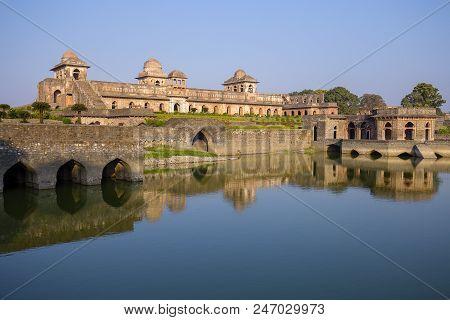 Jahaz Mahal , Ship Palace And Blue Water Lake In Sunrise. Mandu, Madhya Pradesh, India. Old Indian A
