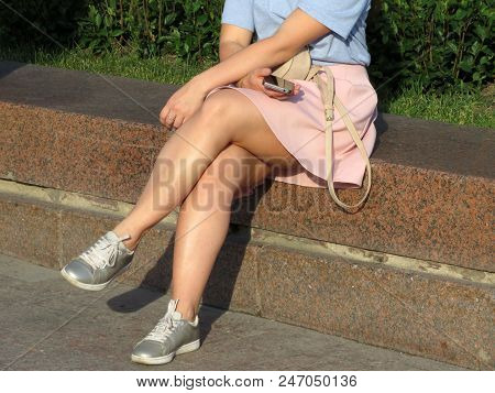 Woman In A Short Skirt And Sneakers Sitting With A Smartphone In Her Hand. Waiting Girl, Naked Legs,