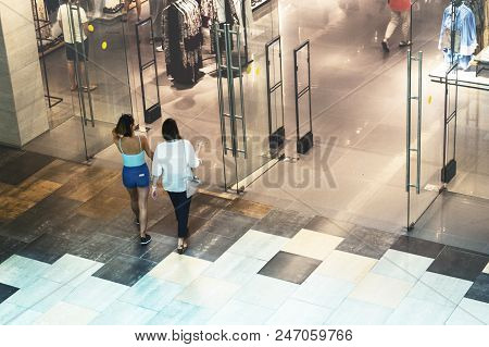 Silhouettes Of Two Women Goes To The Clothing Store. View From Above In Hall Of The Mall. Blur In Mo