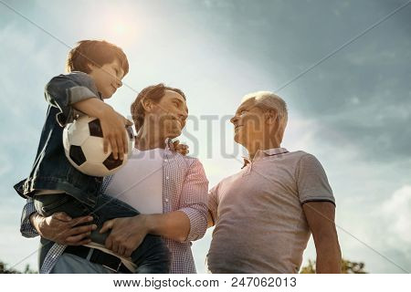 Feeling Proud. Exuberant Smiling Loving Daddy Son And Grandfather Looking At Each Other While The Da