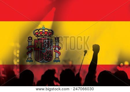 football fans supporting Spain - crowd in stadium with raised hands against Spanish flag