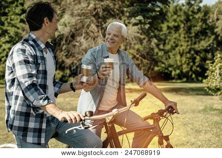Coffee Break. Happy Smiling Vigorous Men Riding Bicycles While Talking And Drinking Coffee