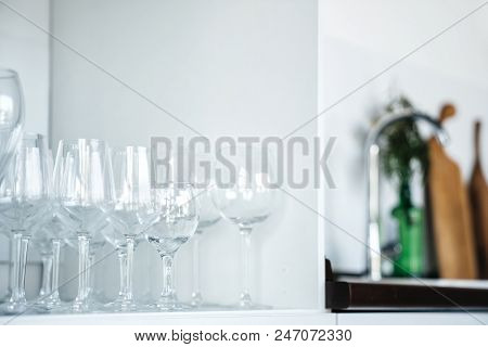 Clean Glass Glasses In The Set On The Shelf In The Light Interior Of The Kitchen. Blurred Clean Back
