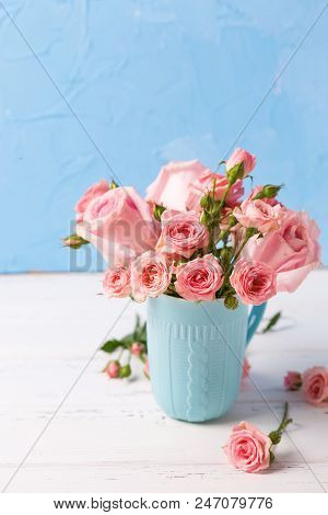 Pink Roses Flowers In Blue Cup Against  Blue Textured Wall. Floral Still Life.  Selective Focus. Pla