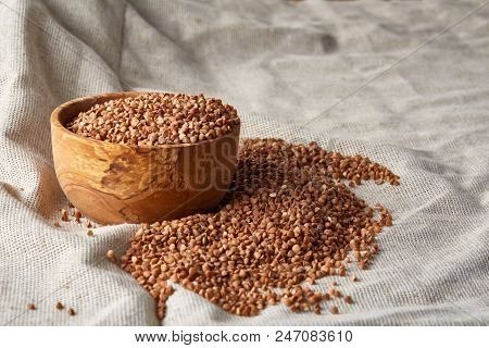 Flax seeds in a wooden plate on homespun tablecloth, top view, close-up, selctive focus. Nutritious and deitary ingredient. Healthy lifestyle concept. Useful oilseed for everyday cooking.Healthy eating, dieting poster