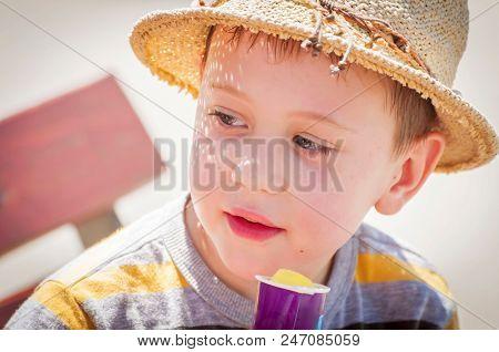 Cute Caucasian Kindergarten Age Child In A Straw Hat Eating Ice Cream Or Frozen Yogurt In The Summer