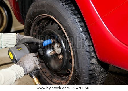 Close-up of mechanic changing wheel on car - with pneumatic wrench