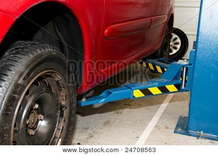 Car on jack ready to change wheel in workshop