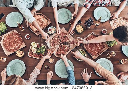Everybody Loves Pizza. Close Up Top View Of Young People Picking Pizza Slices While Having A Dinner
