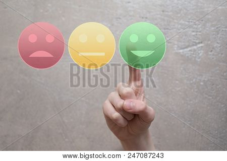 Finger Giving Rating And Review With Happy, Neutral Or Sad Face Icons By Pressing Green Round Happy