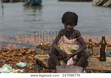 Cacheu, Republic Of Guinea-bissau - February 1, 2018: Young Girl Washing Bottles Next To The Water I