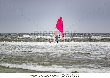Man Windsurfing On Cloudy Windy Cold Day On Romo Island In Denmark