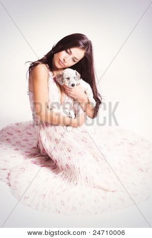 young elegant woman gently holds little puppy, studio shot, small amount of grain added poster