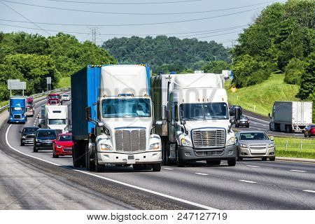 A Highway Packed With Traffic Led By Two Semi-trucks.  Note: All Logos And Identifying Marks Have Be