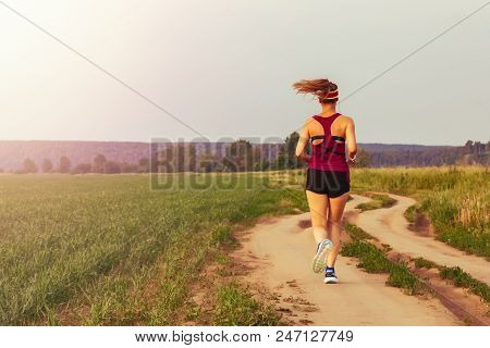 Sport Teenage Girl Running Outdoor. Young Woman Running In Field At Evening. Back View Of Running La